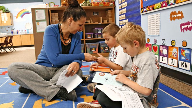 Teacher Amy Trujillo gives stickers to Kalon Hall, center, and Wyatt Walters in her accelerated kindergarten class at Apache Elementary School in Peoria in February.