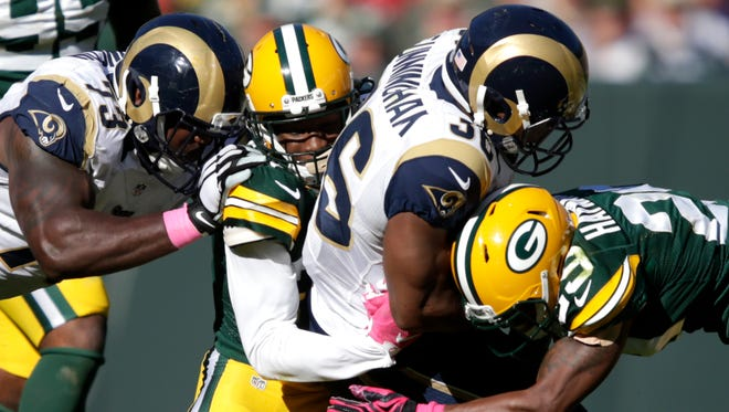Green Bay Packers' Damarious Randall (23) and Green Bay Packers' Casey Hayward (29) tackle St. Louis Rams' Benny Cunningham (36).