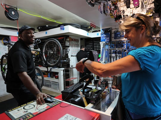 Arley Michel, co-owner of Just Riding Around, assists Lori Robinson, a seasonal North Fort Myers resident, Wednesday morning. The bike shop takes pride in its customer service.