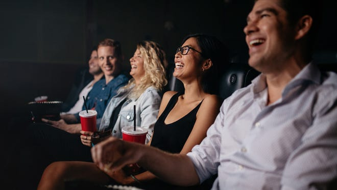 Young people sitting in multiplex movie theater watching movie and smiling.