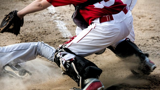 Anonymous youth baseball player slides under the catcher's tag at home plate
