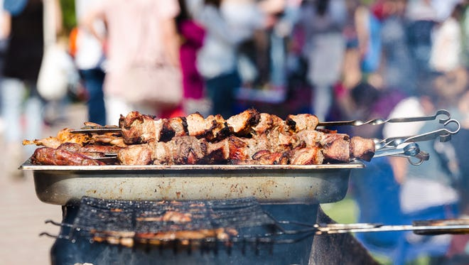 The pork shish kebabs prepared on a brazier for a holiday, blurred people on background, shallow DOF