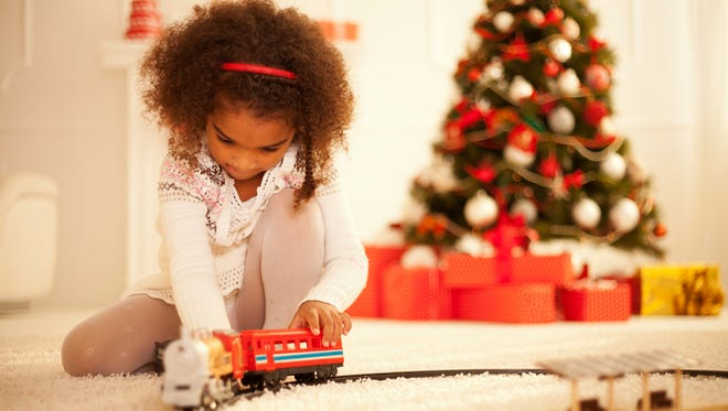 Cute girl enjoy playing with new toy by Christmas tree