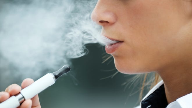 A closeup of a woman smoking an electronic cigarette outdoors.