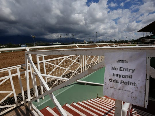 Heavy clouds are seen over the San Gabriel Mountains at Santa Anita Park in Arcadia, Calif., Thursday, March 7, 2019. Extensive testing of the dirt track is under way at eerily quiet Santa Anita, where the deaths of nearly two dozen thoroughbreds in two months has forced the indefinite cancellation of horse racing.