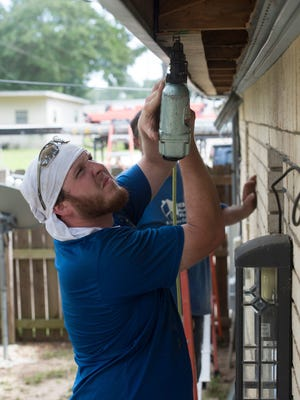 Bailey Coleman a contractor for Rebuild Northwest Florida works to completes a retrofit to the home by adding tress ties and closing off the soffit June 30, 2017.