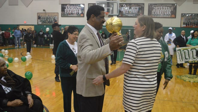 Warhorses coach Charles Smith (left) hugs Peabody principal Janie Henagan after receiving a trophy for his 1,000th win.