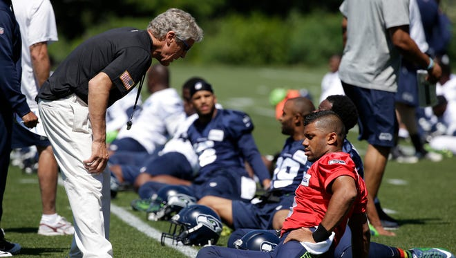 Seattle Seahawks head coach Pete Carroll, left, talks with quarterback Russell Wilson during an NFL football organized team activity Tuesday, June 9, 2015, in Renton, Wash.