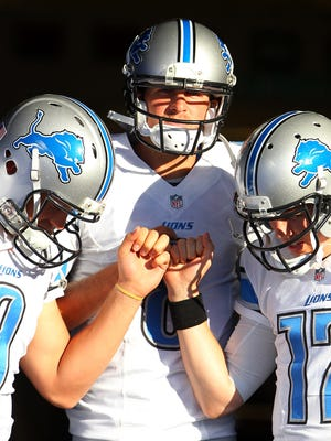Detroit Lions quarterbacks Matthew Stafford (9), Dan Orlovsky and Kellen Moore (17) huddle before a game against the Buffalo Bills on Aug. 28, 2014, in Orchard Park, N.Y.