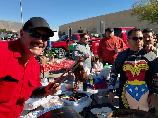 Manny Ponce, left, and friends enjoy a tailgate cookout