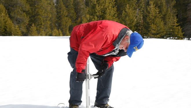 FILE- In this March 1, 2016 file photo, Frank Gehrke, chief of the California Cooperative Snow Surveys Program for the Department of Water Resources, checks the depth of the snowpack at Phillips Station near Echo Summit, Calif. State surveyors will trudge through several feet of snow Wednesday, March 30, 2016, to manually measure what could be close to a normal Sierra Nevada snowpack for this time of year.