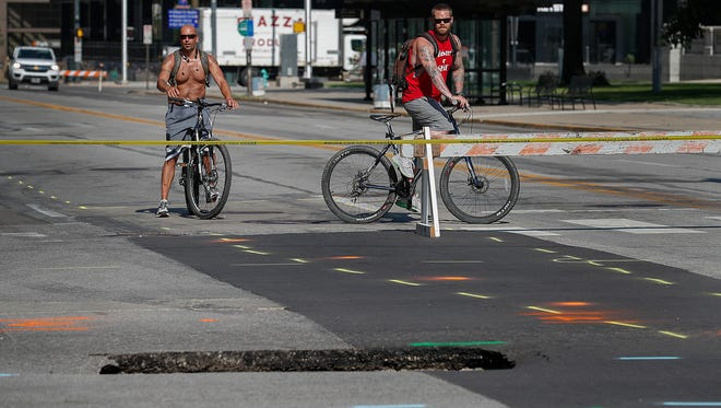 Onlookers stop by to catch a glance  of the sinkhole in the middle of the intersection of Ohio and Pennsylvania Streets Thursday,  July 5, 2018.