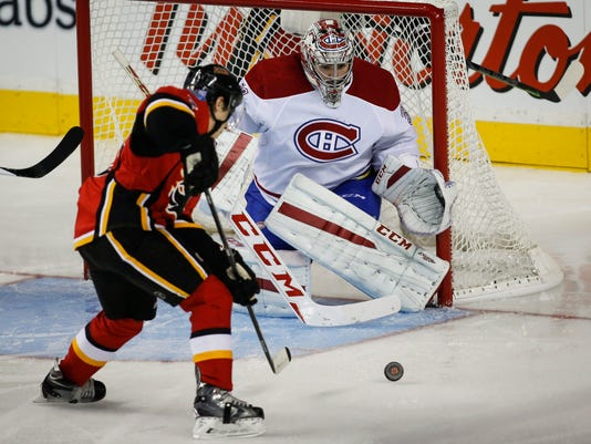 Montreal Canadiens goalie Carey Price, right, blocks the net as Calgary Flames' Johnny Gaudreau tries to score during the second period of an NHL hockey game in Calgary, Alberta, Tuesday, Oct. 28, 2014. (AP Photo/The Canadian Press, Jeff McIntosh)