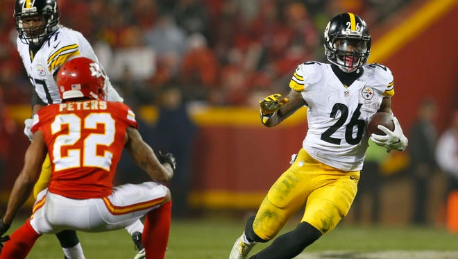 Pittsburgh Steelers running back Le'Veon Bell (26) runs the ball as Kansas City Chiefs cornerback Marcus Peters (22) defends during the second quarter in the AFC Divisional playoff game at Arrowhead Stadium.