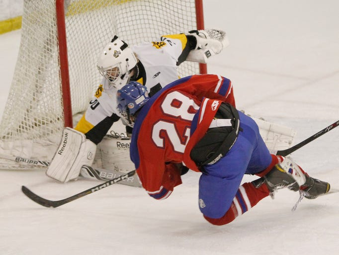 McQuaid's goaltender Tim Brei, left, makes a save against Fairport's Jared Carlston in the class A semifinal.