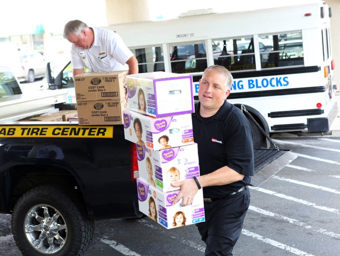 Ryan Allbritton of U.S. Bank carries boxes of diapers. Les Schwab and U.S. Bank collected thousands of diapers for Family Building Blocks last month as part of child abuse prevention month. The nonprofit helps families and children at risk of abuse and neglect, and according to Patrice Altenhofen they use 48,000 diapers per year.