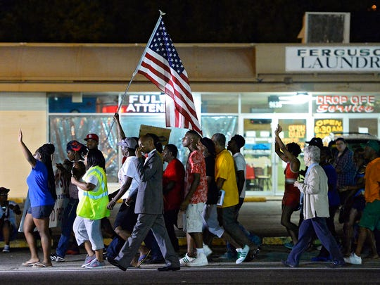 Demonstrators peacefully protest the shooting death of teenager Michael Brown on Aug. 21 in Ferguson, Mo.