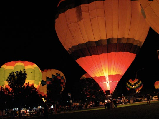 Hot air balloons lit up by the firing of their burners, glow in the night in Page, AZ November 3, 2007.