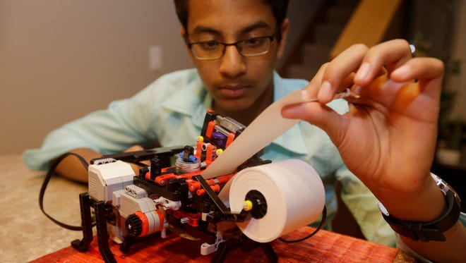 Shubham Banerjee, 13, works on his Lego robotics Braille printer.