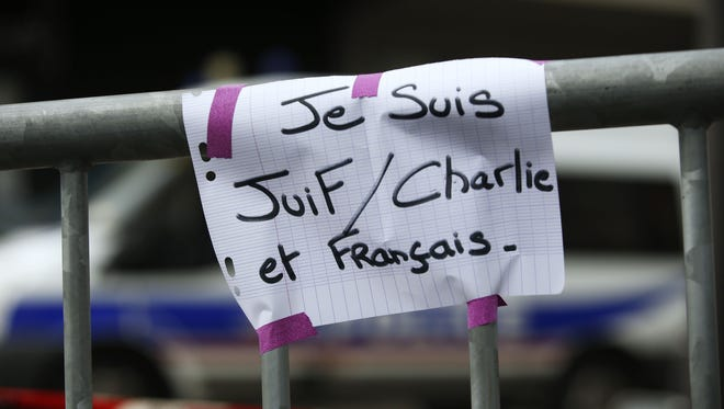 """A board reading """"I am Jewish, Charlie and French"""" near a kosher grocery store in eastern Paris."""