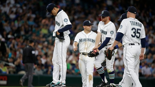 Seattle Mariners starting pitcher Hisashi Iwakuma, left, looks down as he waits to be relieved against the Arizona Diamondbacks in the sixth inning of a baseball game Tuesday, July 28, 2015, in Seattle.