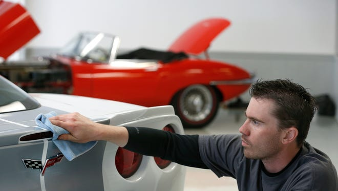 Steve Kosko cleans a 2013 Grand Sport Corvette at Turner Automotive, which has been bought by the Van Bortel Group. A 964 Jaguar sits in the background.