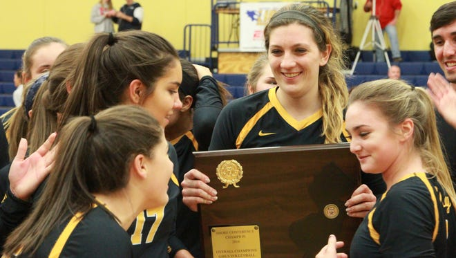 Kim Evans surrounded by her  Lancers teammates and holding the Shore Conference Tournament trophy after St. John Vianney defeated Jackson Liberty.