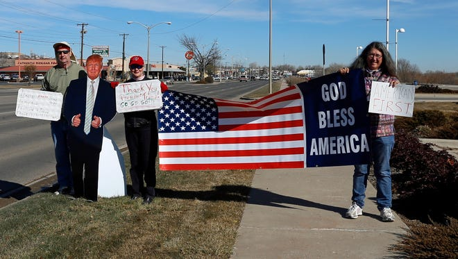 From left, Terry Roberts, Ivy Kauth and Virginia Hatchett hold signs and a flag on Monday during a rally to support President Donald Trump outside Farmington Museum at Gateway Park.