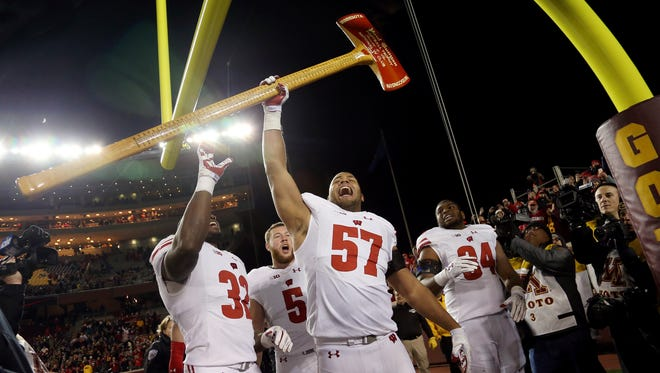 Wisconsin defensive end Alec James (57) holds up Paul Bunyan's Axe after the Badgers beat Minnesota, 31-0, on Saturday.