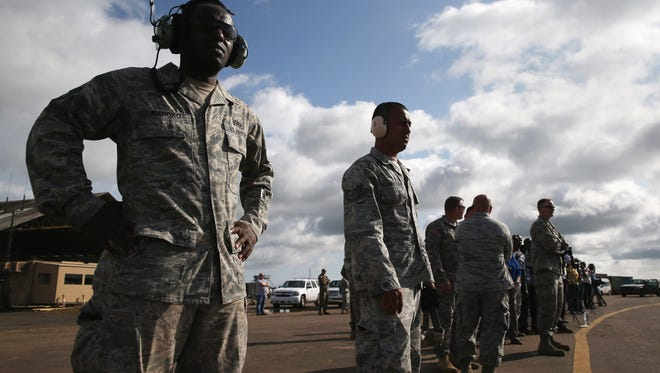 U.S. Air Force airmen watch as U.S. Marines arrive as part of Operation United Assistance on Oct. 9, 2014, in Monrovia, Liberia.
