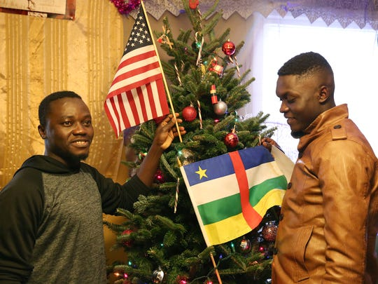 Bonaventure Tajim, left, and Placide Tadjim adding the American flag and the flag of the Central Republic of Africa to the tree.
