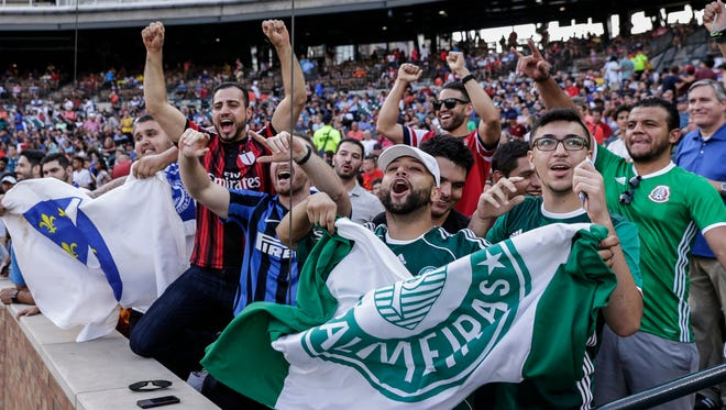 Soccer fans include Abdallah Fahs of Windsor, ON, center, cheer as a TV camera goes by during the International Champions Cup at Comerica Park, July 19, 2017.