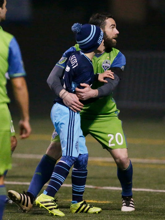 Seattle Sounders defender Zach Scott, right, hugs his son, Kalei Scott, 11, during the first half of the Zach Scott Testimonial Match, Wednesday, March 1, 2017, in Seattle. The match was held to honor Scott, who retired last year after 15 seasons with different incarnations of the club. (AP Photo/Ted S. Warren)
