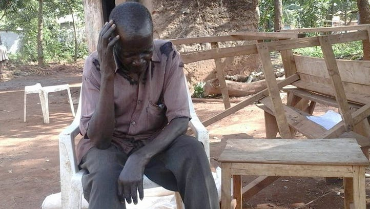 Abdou Mbone, 58, sits under a mango tree on the outskirts