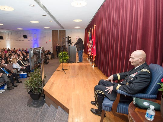 Retired Lt. Gen. Keith Huber, right, sits as musician