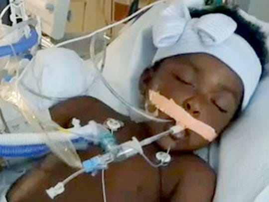 A frame grab from cell phone video shows 2-year-old Laylah Washington lying in a hospital bed the day after being shot in the head during an apparent road rage incident.