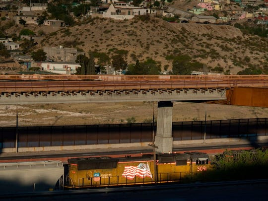 A train runs paralell to the US-Mexico border fence
