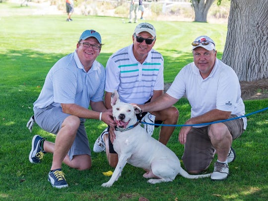 From left, golfers Ron Bruder, Tobe Turpen and Kyler Breen take a moment to pet Pinto the dog at Picacho Hills Country Club at a previous year's Mulligans Fore Mutts Golf Tournament benefiting ACTion Programs for Animals.
