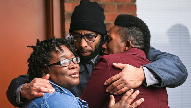 Chris Cleveland hugs his wife Danielle Cleveland, right, and her sister Dominique Wicker as the three stand outside the Broadleaf Arms apartment where Darnell Wicker, who was shot 14 times and killed by two Louisville Metro police officers. On Aug. 8, the daughter of Wicker's girlfriend told dispatchers that he was holding a knife and had broken into her mother's residence at the Broadleaf Arms Apartments in southwestern Louisville. Wicker, who was an African-American Army veteran, was shot to death while holding a tree saw by Officers Taylor Banks and Beau Gadegaard, who were responding to a domestic violence call. Banks and Gadegaard, who are White, ordered Wicker to drop the saw at least five times before firing, according to body cam footage, which was released the same day as the shooting.