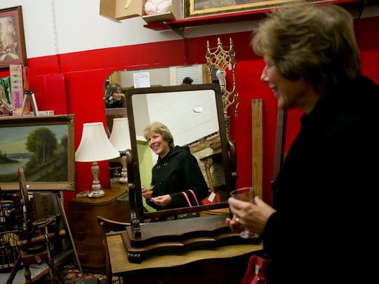 Mary Ellen McDonald sips on a mimosa while looking over antiques with family during the Gourmet Gallop Thursday, Dec. 3, 2015, at Angels Among Us in St. Clair.