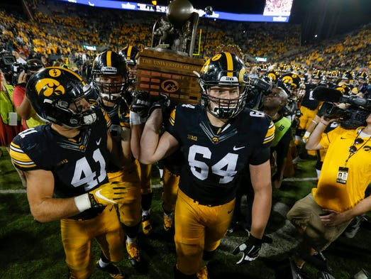Iowa's Bo Bower, left, and Cole Croston carry the Cy-Hawk