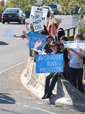 Jerry Bodman and fellow members of Salem 350, a local environmental group, shows support for the Standing Rock Sioux tribe by gathering together and displaying signs during rush hour traffic on Wednesday, Sept. 7, 2016, at the Marion Street Bridge in downtown Salem. The Sioux tribe sued the U.S. Army Corps of Engineers in August, arguing that it did not fully investigate the effects of the Dakota Access Pipeline in North Dakota.