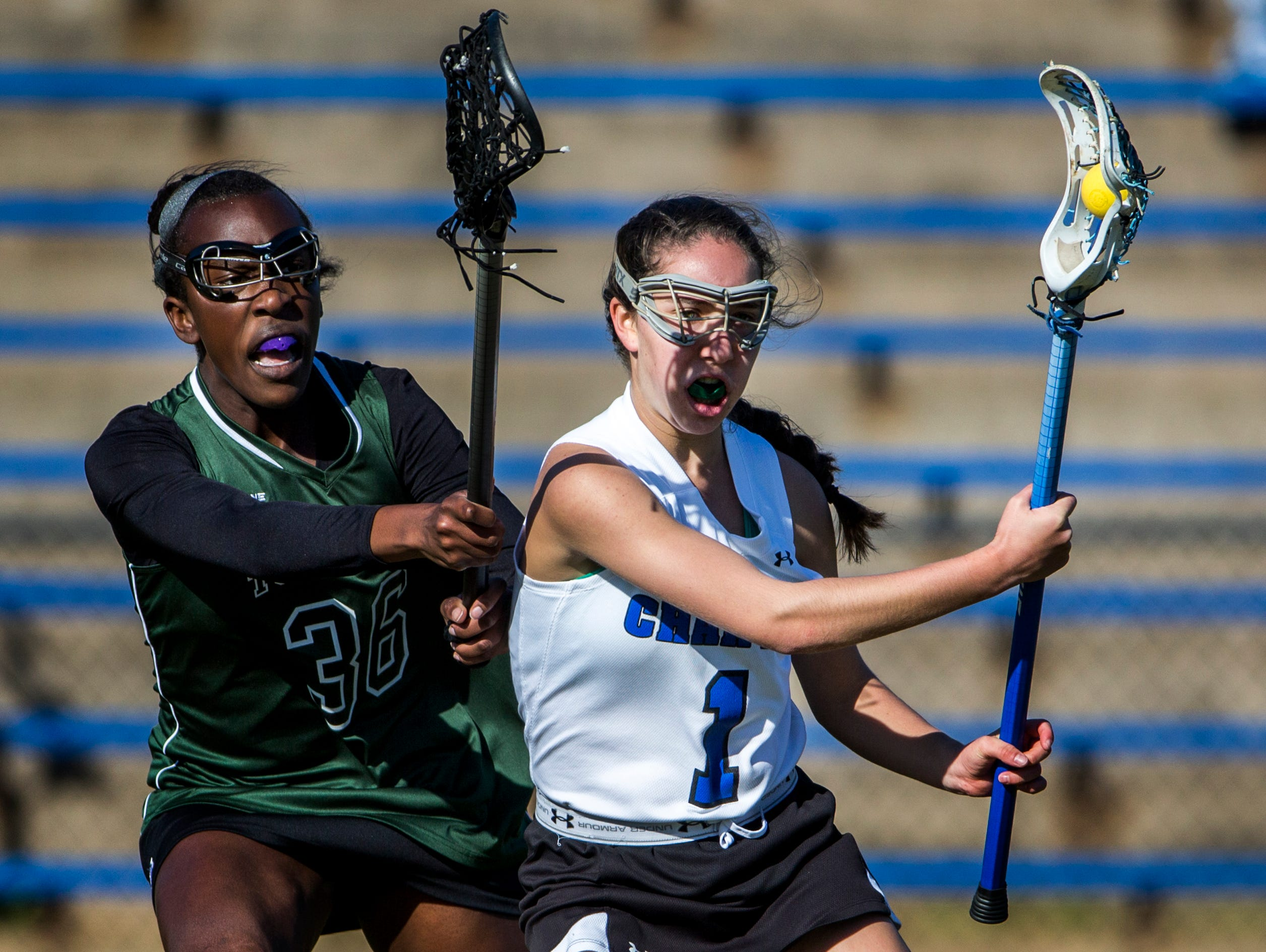 Charter of Wilmington's Michelle Shulkov (1) works around Tower Hill's Jade Olurin during the Force's 10-9 win on March 29. Charter moved into this week's girls lacrosse rankings at No. 3.
