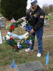 Norb Lankheit decorates the grave of Sgt. Charles Fleek,