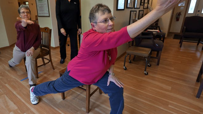 On With Life physical therapist Gail McGaughy, center, looks on as Connie Ramseyer, left, of Altoona, and Cheryl Weber, right, of Runnells, participate in a program offered to people with Parkinson's Disease at On With Life in 2014.
