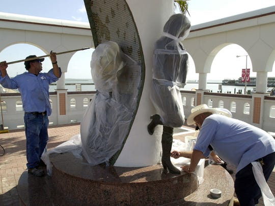 Robert Alaniz (left) and Bert Vargas (cq)(right) with the city's Park Maintenance Department, repaint some of the area around the Selena Statue in July 2000 where people had written graffiti. They covered the statue and flower to keep from getting paint on them.