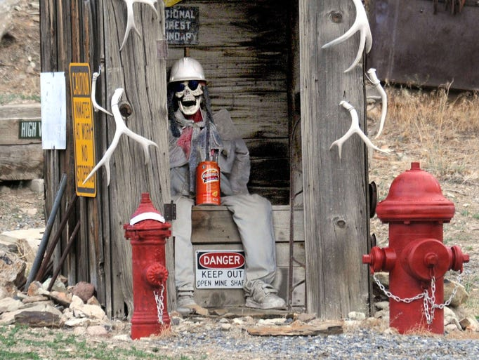 This outhouse in the historic town of Manhattan has an unusual visitor not to mention a number of signs sort of indicating why he looks like he does as does the jug of Metamucil in his lap.