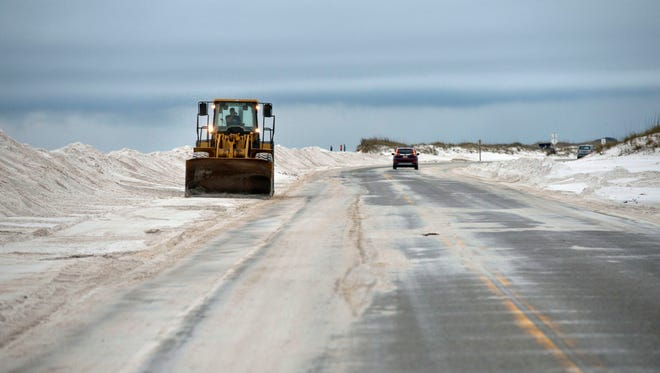 National Park officials work Dec. 30 on clearing wind blown sand from Fort Pickens Road.