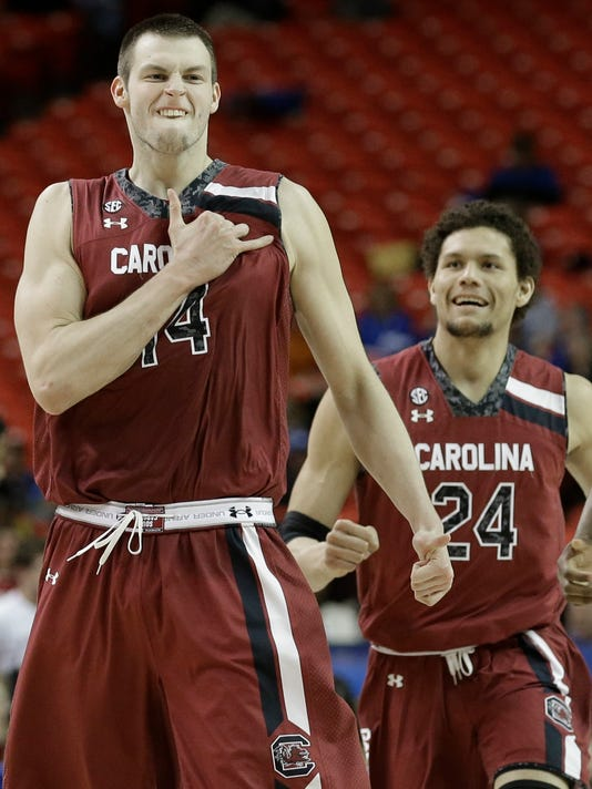 South Carolina forward Laimonas Chatkevicius (14) celebrates after the team beat Arkansas 71-69 after the second half of an NCAA college basketball game in the second round of the Southeastern Conference men's tournament, Thursday, March 13, 2014, in Atlanta. (AP Photo/Steve Helber)