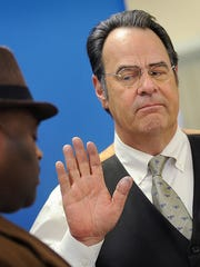 Comedian, singer and actor Dan Aykroyd, right, is sworn-in as a reserve deputy of the Hinds County Sheriff's Department by then-Sheriff Tyrone Lewis in 2014.